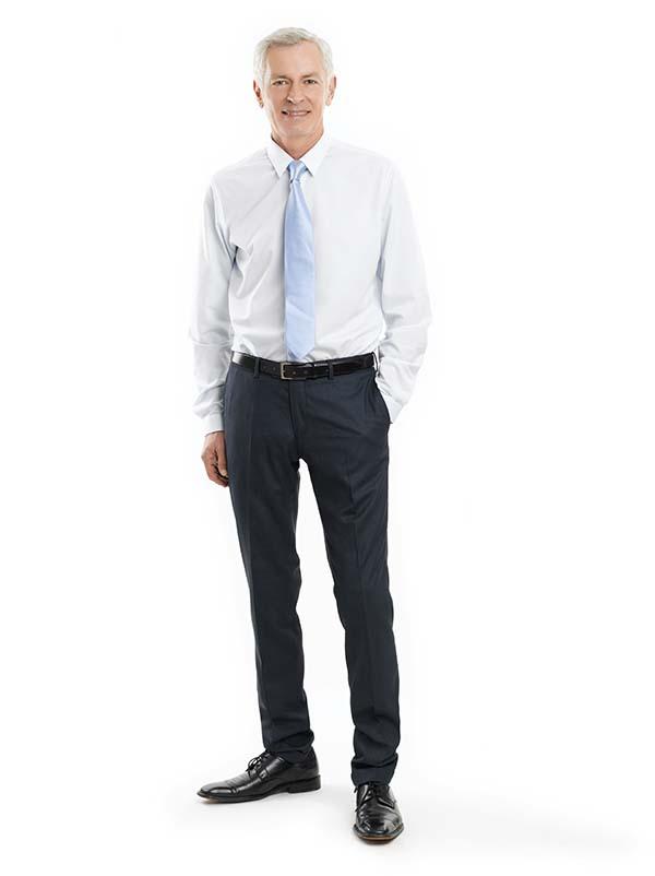 Full-length portrait of a senior businessman standing against white background.